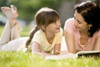 Mom and child on lawn reading